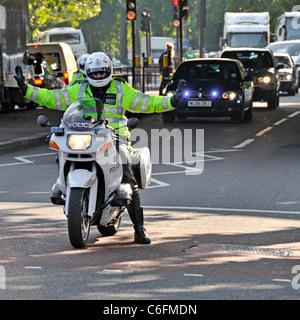 Agent de police métropolitaine sur l'escorte de motos BMW piétons holding off crossing Banque D'Images