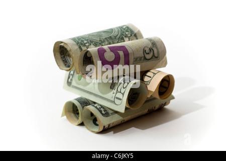 La construction de l'argent. Image conceptuelle avec billets roulés empilés les uns sur les autres sur un fond blanc Banque D'Images