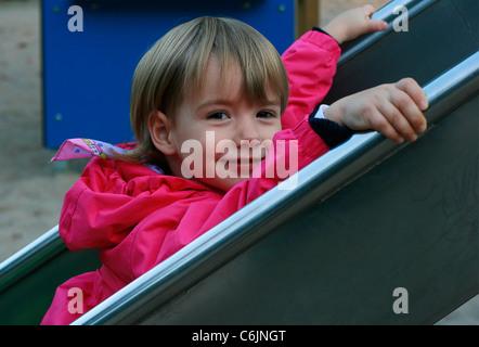 Une jeune fille allemande glissant le long d'une glissière. Banque D'Images