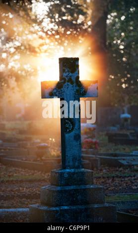Croix de cimetière pierres tombales éclairée le début de la lumière du soleil du matin à travers le brouillard. Banque D'Images