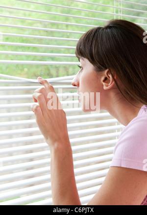 Femme regarde out window Banque D'Images