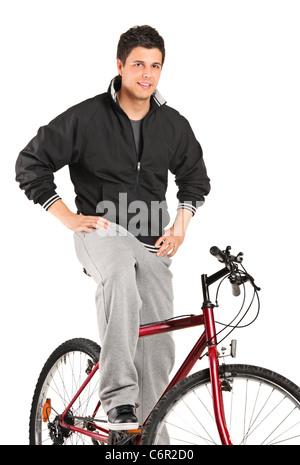 Un jeune garçon posant sur un vélo Banque D'Images