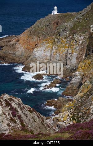 La côte ouest robuste avec haut de la lumière du phare sur l'île de Lundy, Devon, Angleterre Royaume-uni en Août Banque D'Images