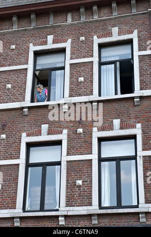 Femme regardant par sa fenêtre dans la ville Dinant, Ardennes, Belgique Banque D'Images