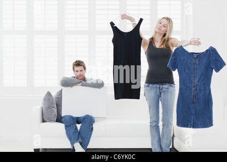 Woman picking des vêtements dans la salle de séjour Banque D'Images