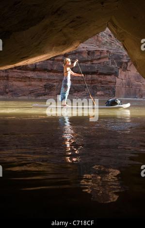 Woman on paddle board à l'avant de la grotte tout en rafting la partie basse de la Rivière San Juan, Mexican Hat, Banque D'Images