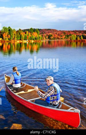 Les gens le canoë sur le pittoresque lac à l'automne, le parc Algonquin, Canada Banque D'Images