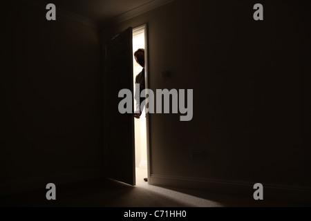 Silhouette d'un homme debout à l'extérieur d'une pièce sombre à la recherche en. Banque D'Images
