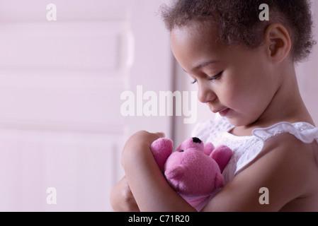 Little girl holding teddy bear affectueusement Banque D'Images