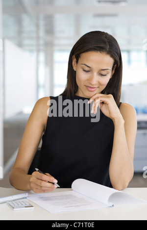 Businesswoman reading document, portrait Banque D'Images