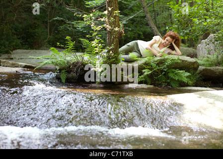 Young woman relaxing on rock par l'écoulement de l'eau Banque D'Images