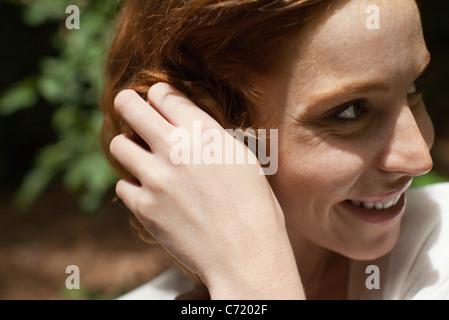 Souriante jeune femme avec la main dans les cheveux, vue latérale
