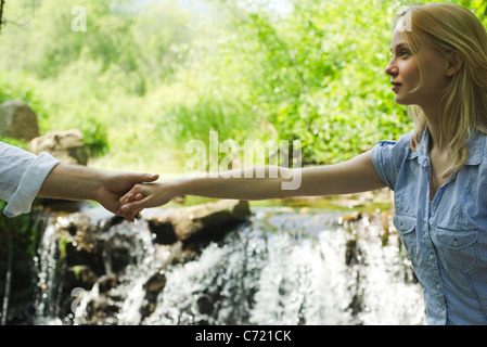 Young woman holding hands with boyfriend par cascade, cropped Banque D'Images