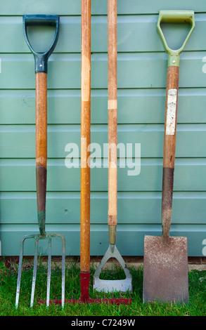 Bien utilisé jardin/ Outils de jardinage appuyé contre le côté d'un abri de jardin - y compris une fourche, râteau, Banque D'Images