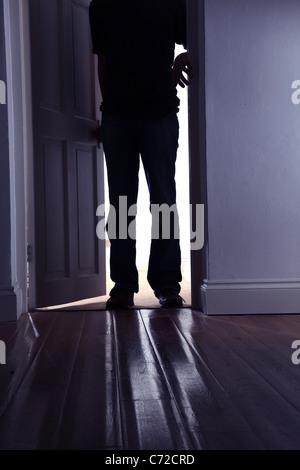 La figure masculine dans une pièce sombre. Banque D'Images