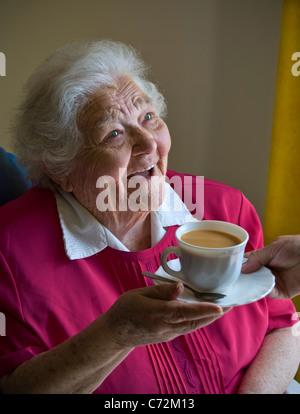 Soins du thé âgés alerte heureuse personne âgée retraité âgée madame reçoit une tasse de thé de son compagnon de voiture sa chambre lumineuse et aérée