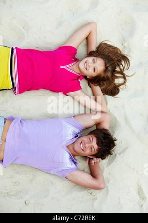 Au-dessus de l'angle d'adolescent joyeux couple lying on sandy beach Banque D'Images