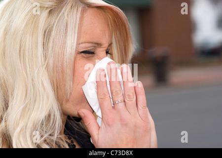 Cette jeune femme d'éternuer dans un mouchoir, soit a un rhume ou allergies vraiment mauvais. Banque D'Images