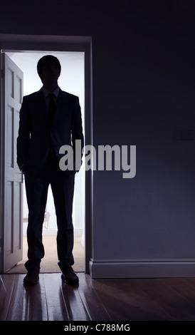 Silhouette d'un homme debout devant une porte ouverte. Banque D'Images