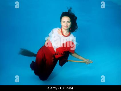 Une jeune femme avec de grands cheveux de poser dans un pool underwater Banque D'Images