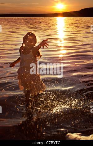 Petite fille heureuse aux projections d'eau dans le lac Banque D'Images