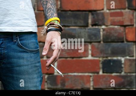 L'adolescent tatoué tenant un joint de cannabis