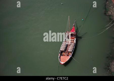 Rivière traditionnelle barge transportant des tonneaux de vin. Douro, Porto d'un pont Banque D'Images