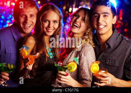 Image de deux couples heureux holding glasses de cocktails Banque D'Images