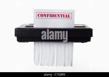 Un document confidentiel avec sur son aspect déchiqueté dans une déchiqueteuse Banque D'Images