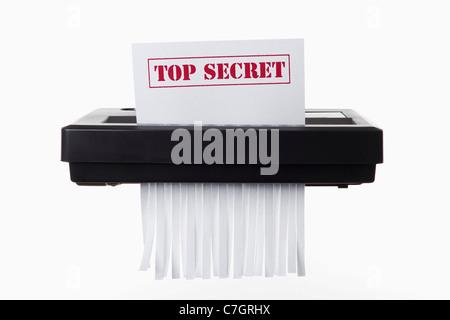 Un document avec TOP SECRET sur son aspect déchiqueté dans une déchiqueteuse Banque D'Images