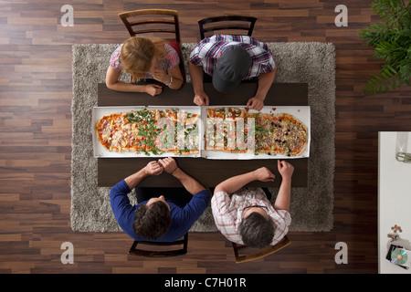 Quatre amis se préparent à manger deux grandes pizzas, overhead view Banque D'Images