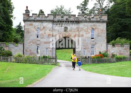 Un père et une mère avec ses deux enfants à pied par le gate house ou maison de gardien à Cholmondeley Castle Cheshire, Banque D'Images