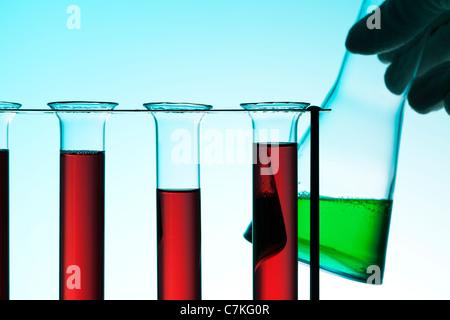 Scène laboratoire chimique, tubes à essai en rack avec un liquide rouge, hand holding Erlenmeyer contenant un liquide Banque D'Images
