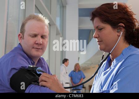 Infirmière mesurant une pression artérielle du patient Banque D'Images