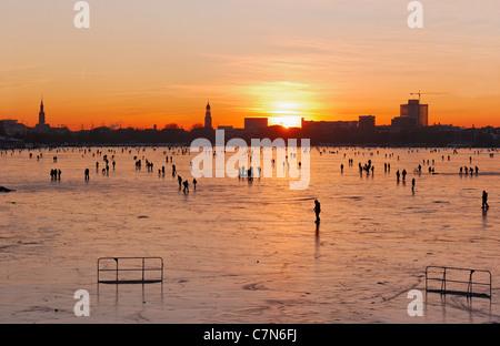 Congelés fermement, l'Aussenalster Lac Alster, après le coucher du soleil, les gens, l'amusement, glace, neige, hiver, Hambourg, Allemagne