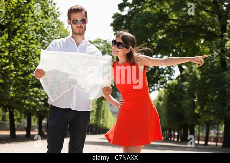 Man reading a map avec une femme qui pointe, terrasse de l'Orangerie, Jardin des Tuileries, Paris, Ile-de-France, Banque D'Images