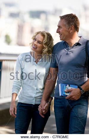 Un couple marche main dans la main, près de la Tamise Banque D'Images