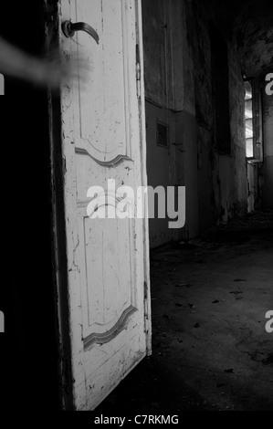Main sur une porte de chambre manoir abandonné Banque D'Images