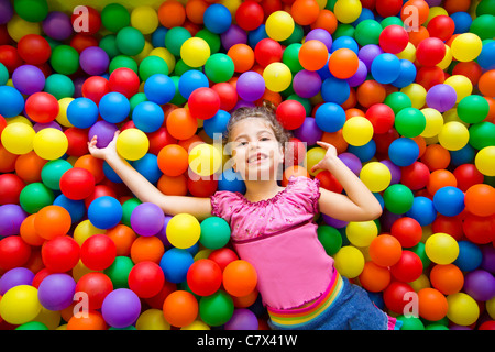 Enfant fille jouant sur l'aire de jeux de boules colorées high view Banque D'Images