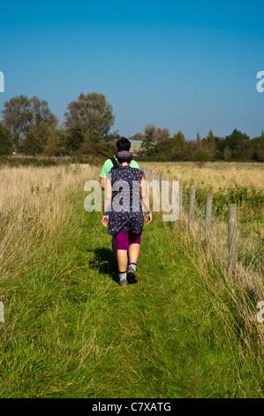 Vue arrière d'un jeune couple de randonneurs marcheurs marcher sur un sentier à travers la campagne du Sussex de Banque D'Images