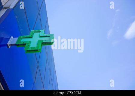 La croix verte affiche à l'extérieur une pharmacie Banque D'Images
