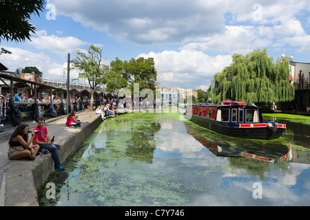 Les jeunes gens assis le long des rives de la Regent's Canal à Camden Lock, au nord de Londres, Angleterre, RU Banque D'Images