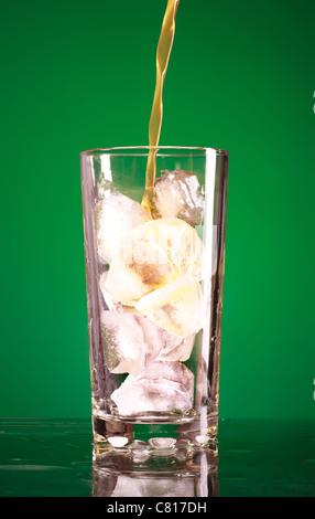 Verser dans le verre de soude sur fond vert Banque D'Images