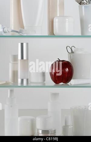 Armoire à pharmacie pleine de produits de beauté et d'une pomme rouge Banque D'Images