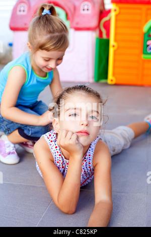 Belle petite little girls lying on floor jouant dans Jeux pour enfants Banque D'Images