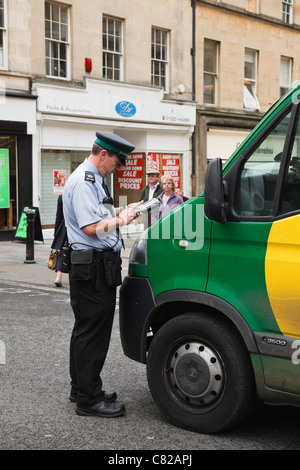 Gardien de la circulation civile ou agent de l'émission d'un billet pour une infraction de stationnement livraison Banque D'Images