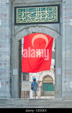 Un visiteur de la mosquée bleue à Istanbul avec un grand drapeau turc accroché au-dessus. Banque D'Images