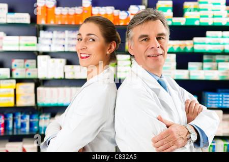 Deux Pharmaciens, debout dans une pharmacie ou pharmacie en face d'étagères avec des produits pharmaceutiques Banque D'Images