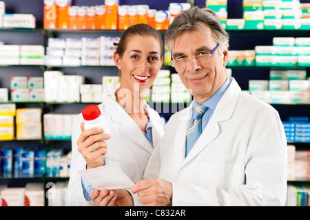 Deux pharmaciens avec des produits pharmaceutiques dans la main de se consulter dans une pharmacie Banque D'Images