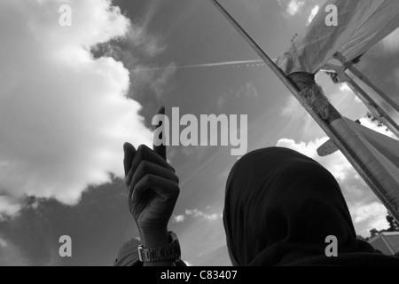 Man's hand pointing to sky avec montre bracelet visible comme femme de Hajib regarde pendant Eid Al-Fitr célébration Banque D'Images